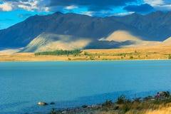 Les couples se reposent à côté du lac de turquoise Photographie stock