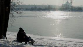 Les couples se reposent sur la réflexion admirative de banc des rayons du soleil en rivière en hiver banque de vidéos