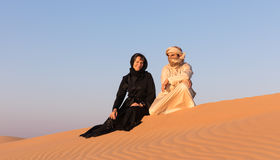 Les couples se sont habillés dans l'habillement arabe traditionnel dans le désert Photographie stock