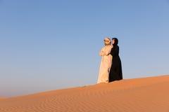 Les couples se sont habillés dans l'habillement arabe traditionnel dans le désert Photos libres de droits