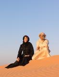 Les couples se sont habillés dans l'habillement arabe traditionnel dans le désert Photos stock