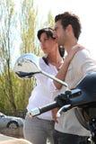 Les couples se sont tenus prêt leur scooter Photographie stock