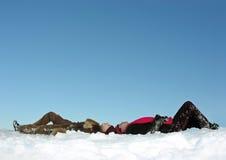 Les couples se trouve sur la neige et la montre vers le haut Photo libre de droits