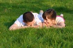Les couples se trouvent sur l'herbe Photos stock