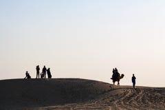 Les couples silhouettés de groupe de famille sur le désert de chameau aménagent en parc photos stock
