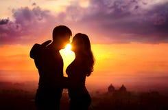 Les couples silhouettent au coucher du soleil Photo libre de droits