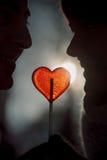 Les couples silhouettent en lucette de forme de coeur de prise d'amour Photo libre de droits