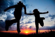 Les couples silhouettent le fonctionnement au coucher du soleil photos libres de droits