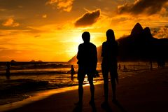 Les couples silhouettent par coucher du soleil dans la plage Photos stock