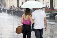 Les couples sous le parapluie marchant en été lourd pleuvoir Photo stock