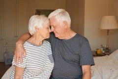 Les couples supérieurs affectueux se reposant avec leurs yeux se sont fermés sur leur lit ensemble Photo libre de droits