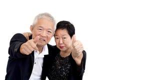 Les couples supérieurs asiatiques dans les affaires attire montrer le thum de geste de main Photo libre de droits
