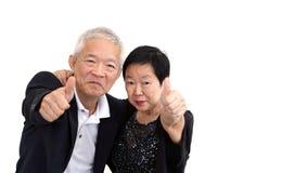 Les couples supérieurs asiatiques dans les affaires attire montrer le thum de geste de main Photographie stock libre de droits