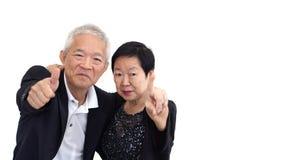 Les couples supérieurs asiatiques dans les affaires attire montrer le thum de geste de main Image stock