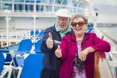 Les couples supérieurs d'amusement donnent des pouces sur la plate-forme du bateau de croisière Photo stock