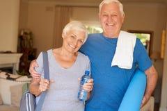 Les couples supérieurs de sourire se sont préparés au yoga se tenant ensemble à la maison Photo stock