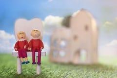 Les couples supérieurs de vieille poupée s'asseyent sur l'herbe verte pour la maison et le sav Photos stock