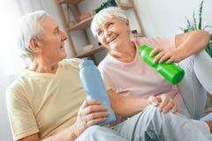 Les couples supérieurs exercent ensemble à la maison le rafraîchissement d'eau potable de soins de santé image libre de droits