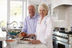Les couples supérieurs font le repas de la Turquie de rôti dans la cuisine ensemble images stock