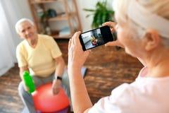 Les couples supérieurs s'exercent ensemble à la maison prenant des photos avec la bouteille d'eau Image stock