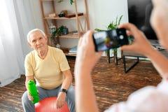 Les couples supérieurs s'exercent ensemble à la maison prenant des photos avec le plan rapproché de bouteille d'eau Photos libres de droits