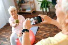 Les couples supérieurs s'exercent ensemble à la maison prenant des photos avec la pomme image stock