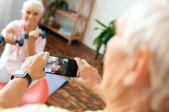 Les couples supérieurs s'exercent ensemble à la maison prenant des photos sur la boule d'exercice Image libre de droits