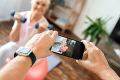 Les couples supérieurs s'exercent ensemble à la maison prenant des photos sur le plan rapproché de boule d'exercice Image stock