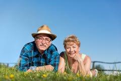 Les couples supérieurs se trouvant l'été mettent en place dans l'herbe verte Images stock