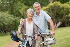 Les couples supérieurs sur le cycle montent au parc Photographie stock