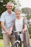 Les couples supérieurs sur le cycle montent au parc Images stock