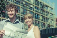 Les couples sur l'avant de la nouvelle maison avec le modèle projettent Photos libres de droits