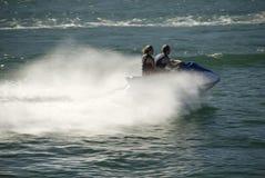 Les couples sur l'avion à réaction skient sur l'eau bleu-vert Images stock