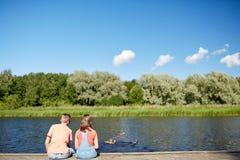 Les couples sur la rivière amarrent à quai regardant des canards de natation Images libres de droits