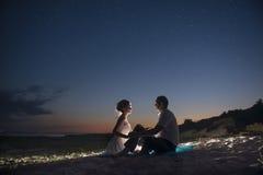 Les couples sur le bord de la mer la nuit Photographie stock