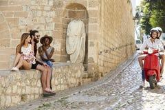 Les couples sur le scooter montent les amis passés s'asseyant sur un mur, Ibiza Photos libres de droits