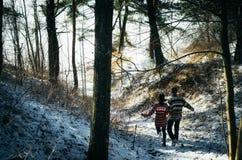 Les couples tenant des mains fonctionnent loin à la forêt photos stock