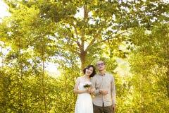 Les couples tenant la promenade arment dans le bras sur le fond vert de forêt photos libres de droits