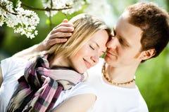 Les couples tendres dans l'amour étreignent sous les fleurs de floraison en parc dans le spri Images stock