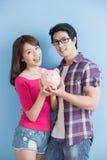 Les couples tiennent la tirelire rose Photo stock