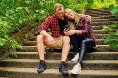 Les couples urbains détendant sur les étapes dans la région sauvage se garent Photo libre de droits
