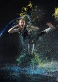 Les coups de pied élevés de femme dans l'eau colorée éclaboussent photo stock