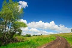 Les courbes de route de campagne d'été en escaladant une colline avec l'herbe verte Cumulus sur le ciel bleu photo stock