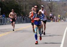 Les coureurs masculins emballe vers le haut de la colline de immense chagrin pendant le marathon de Boston le 18 avril 2016 à Bos Images libres de droits