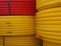 Les couronnes du câble électrique épaisses énormes sont rouge jaune et lumineux lumineux, courbé dans les cercles doux Photos stock