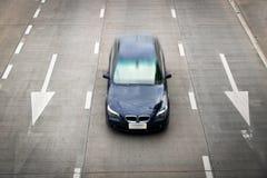 Les courses d'automobiles bleues de vue supérieure et la flèche blanche se connectent la route Photographie stock