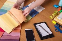 Les couturières de mains prennent le tissu pour la couture, près des outils et du carnet Images libres de droits