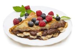 Les crêpes faites maison ont servi avec de la crème de chocolat, les myrtilles fraîches et les framboises, sucre en poudre sur un Photos libres de droits