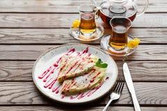 Les crêpes minces délicieuses ont servi avec de la sauce à fraise sur une table rustique en bois Images stock