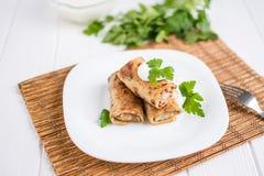 Les crêpes ont rempli de la viande bourrant d'un plat blanc Photos libres de droits